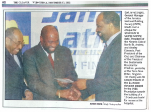 Earl Jarrett hands over a cheque, The Gleaner